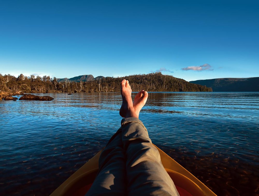 idyllic shot of a man's crossed legs, bare foot floating in a canoe on a lake