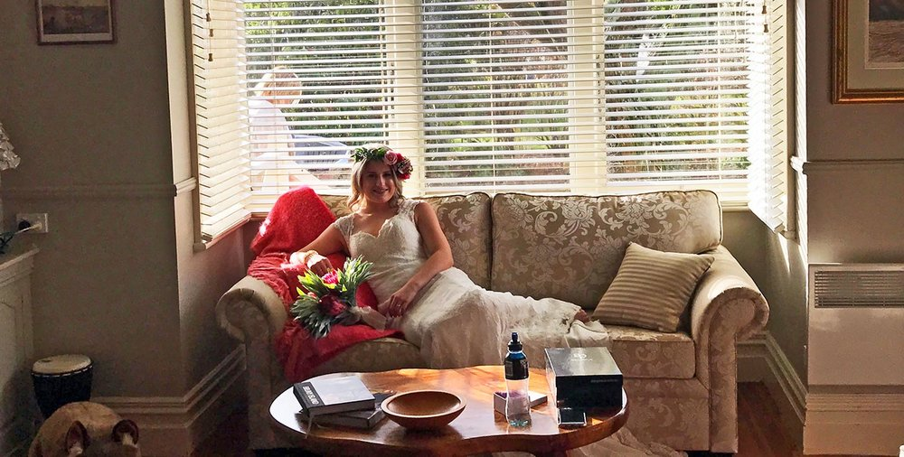 glencoe country b&b - bride laying on a sofa in the lounge room in her wedding dress holding a bouquet of flowers