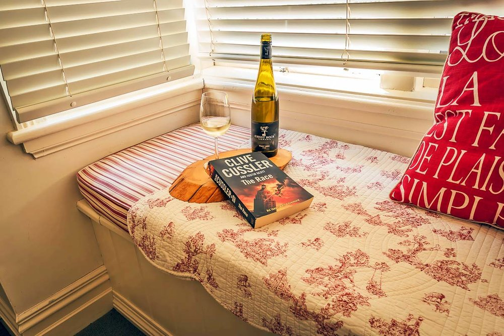 glencoe country b&b comfy window seat with bottle of wine, half a glass of wine and a novel