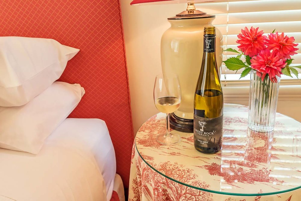 glencoe country b&b bottle of wine and half a glass of wine on the bedside table